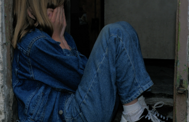 Image of young girl hiding face with hands